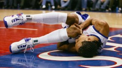 This is a photo of a generic basketball player clutching his knee in agony, much like I did at a city park in Austin.