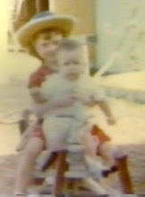 My sister holds me while we ride my horse when he was still fresh and new.