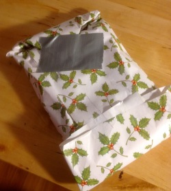 Some people frown on using duct tape, but if it's on the bottom, no one should care, and besides, it's the superior product for covering accidental holes in the wrapping.