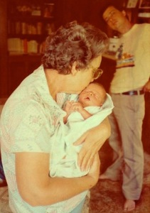 My mother gives her grandson, Aaron, a smooch. That's me, a lot younger and a lot skinnier, in the background.