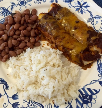 Chicken mole enchiladas on the plate, along with cumin rice and pinto beans!