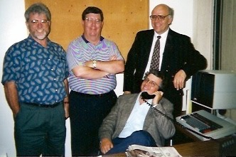Why are these men smiling? That's me seated in my office on Black Tuesday with members of my staff, from left, Copy Chief Steve Howland, Page One Copy Editor Bill Gould, and Assistant News Editor Larry Lovelace. The photo taken by former colleague Gail Smith, one of our Women of Wire. Congratulations to all of us for making it out of the newspaper business alive!