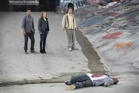The guy on the ground had been shot in the chest a couple times before going on a rampage and nearly killing our heroes. They finally being 86'd the guy by running over him with their pickup truck. While they do look somewhat aghast, they don't look quite as freaked out as one might expect.