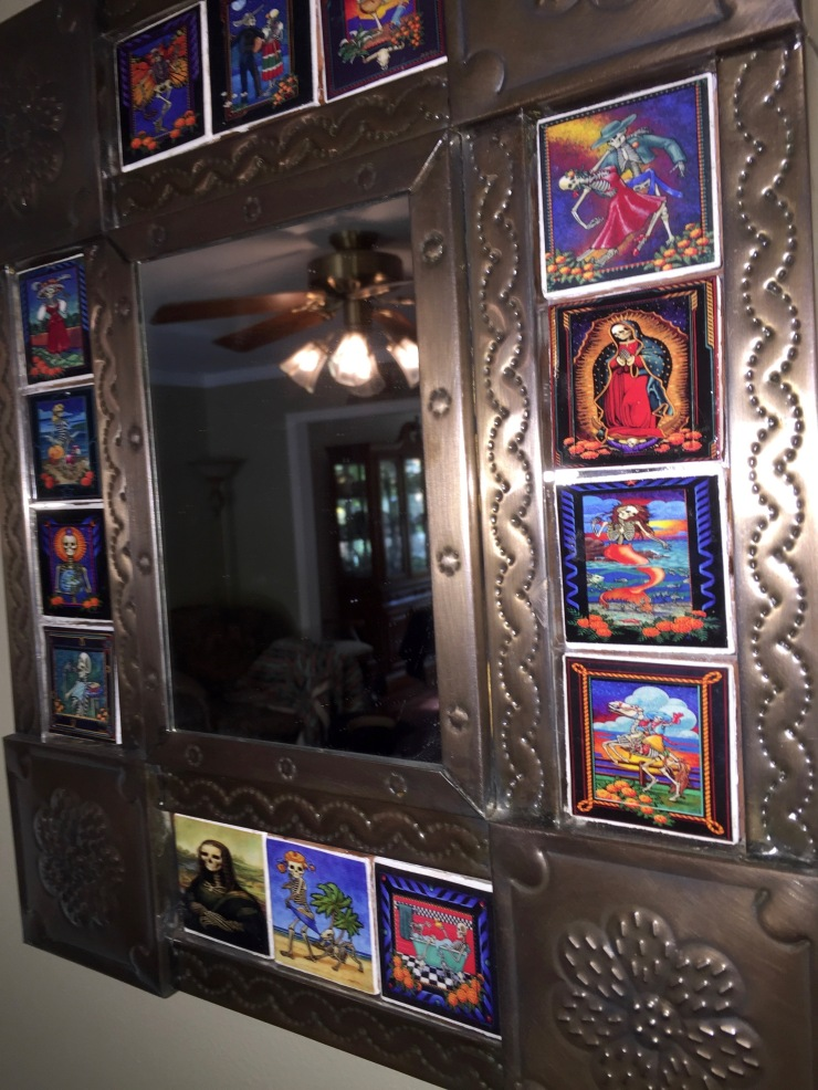 This pressed-tin mirror with imbedded Dia de los Muertos tiles is right by the front door, and is a permanent fixture in our living room, not a Halloween decoration.