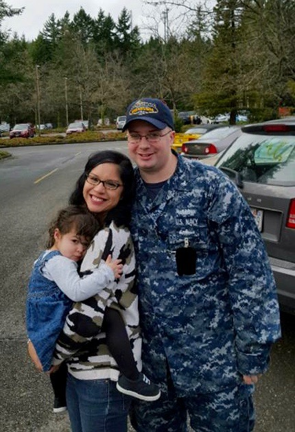 Aaron, just home from his last deployment, with his wife and daughter. With his Navy stint drawing to a close, he and his family will soon be sailing uncharted waters.