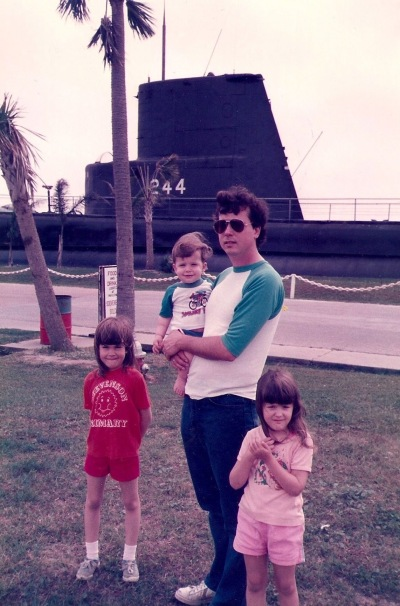 With a submarine in the background, I hold Aaron in 1985 at Seawolf Park in Galveston, Texas, with his older sisters along on the trip.