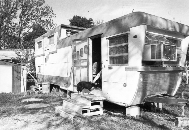 Our first home was this 1956 Pacemaker trailer parked on the wrong side of the tracks in Austin, Texas. I lived there through college, and that's my arm dragging my dog, Wilson, inside while a student photographer prematurely snapped the picture.